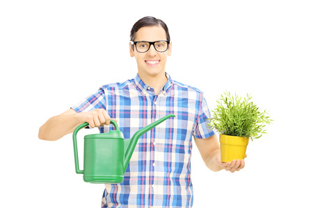 moisten: Young man holding watering can and flowerpot, isolated on white background Stock Photo