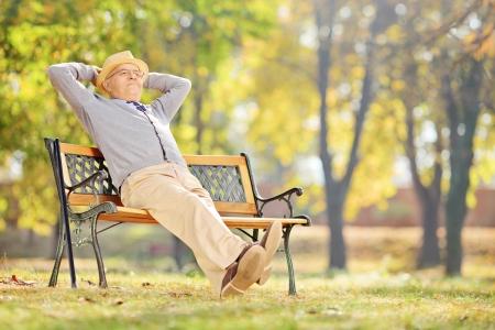 relaxando: Cavalheiro mais velho sentado em um banco de madeira e relaxar em um parque