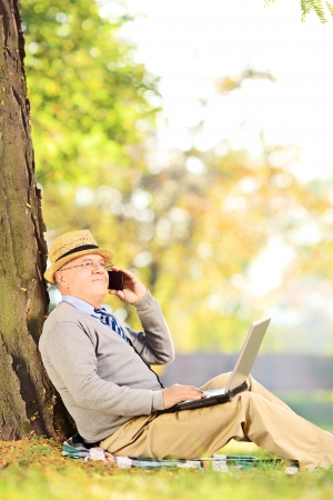 Senior man in park talking on a cell phone and working on laptop photo
