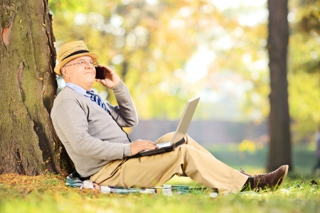 Senior man in park talking on a mobile phone and working on laptop photo