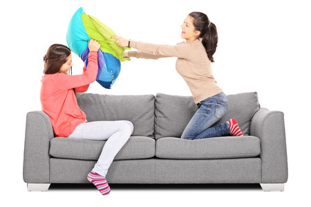 Two young girls having a pillow fight seated on sofa, isolated on white background photo