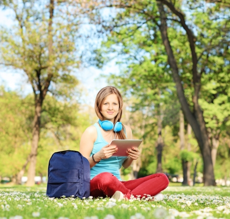 Young female student with headphones and tablet sitting in park, shot with a tilt and shift lens photo