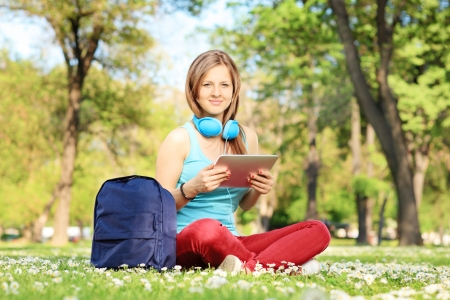 Young female student with headphones and tablet sitting in a park photo