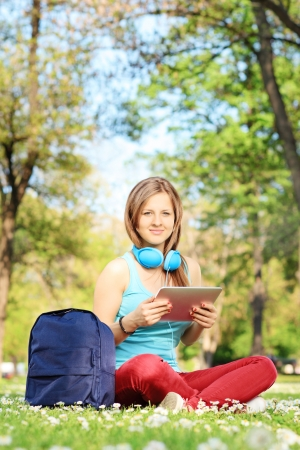 Young female student with headphones and tablet sitting on green grass in park photo