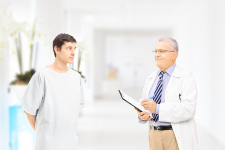hospital gown: Young male patient talking to doctor in hospital corridor Stock Photo
