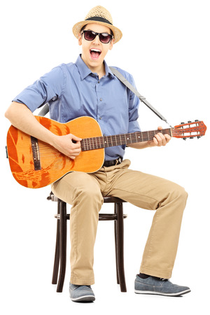 guitarra acustica: Un joven sentado en una silla y tocando la guitarra acústica, aislado en fondo blanco