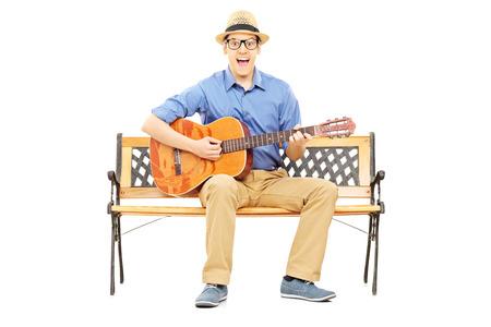 hombre sentado: Emocionado joven tocando la guitarra acústica sentado en un banco aislado en el fondo blanco