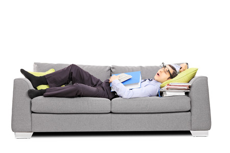 tired businessman: Exhausted young accountant sleeping on a couch, isolated on white background Stock Photo