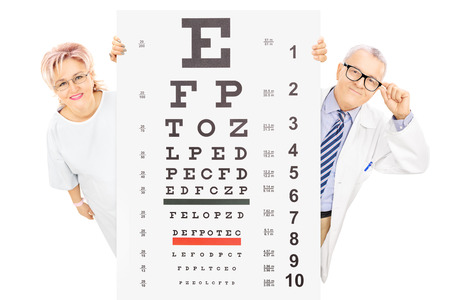 Middle aged male doctor and female patient standing behind eyesight test isolated on white background photo