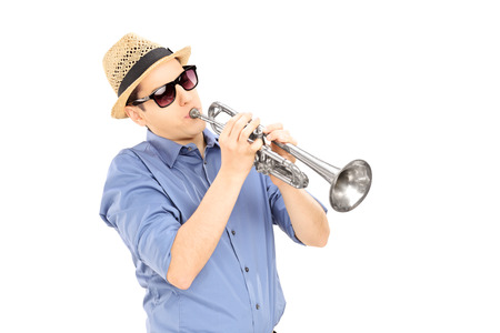 Young male musician with sunglasses playing trumpet, isolated on white background