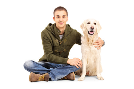 Young man in casual clothes sitting on floor with his Labrador retriever dog isolated on white background photo