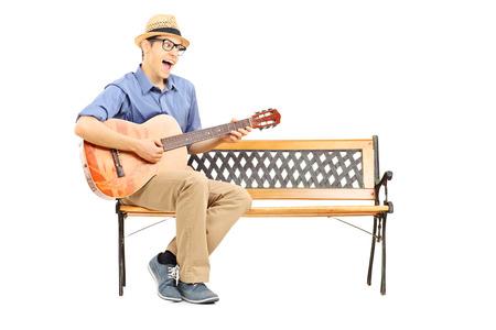 hombre sentado: Joven guitarrista extático sentado en el banco y el canto aislado en fondo blanco