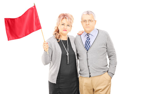 Middle aged couple waving a red flag, isolated on white background photo