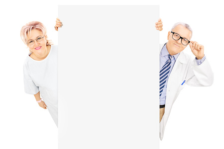 Middle aged male doctor and female patient standing behind blank panel isolated on white background photo