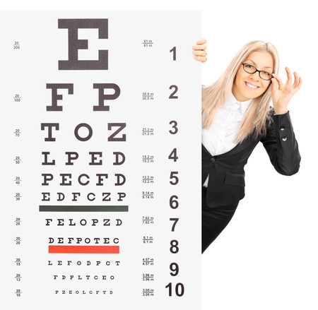 tilt shift: Smiling young woman standing behind an eyesight test isolated on white background shot with a tilt and shift lens Stock Photo