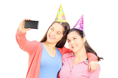 Two teenage girls taking pictures of themselves with cell phone, isolated on white background photo