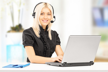 Young female customer service operator working on laptop in office photo