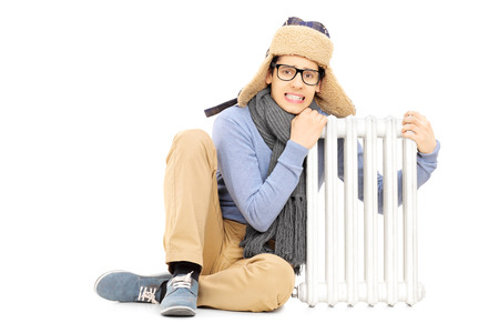 shiver: Freezing young guy in winter hat and scarf sitting next to radiator isolated on white background Stock Photo