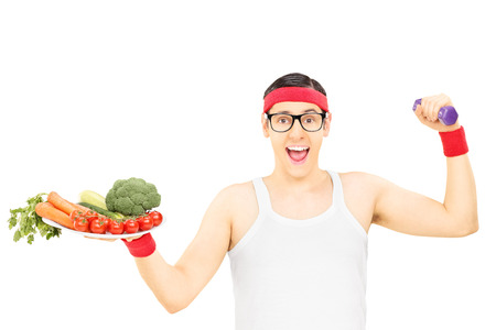 Nerdy guy holding plate with vegetables and a dumbbell isolated on white  photo