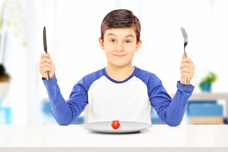 young knife: Young boy holding fork and knife with cherry tomato on a plate in front of him at home