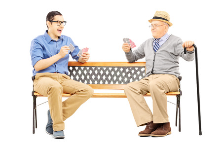 Young man and senior gentleman playing cards seated on a bench isolated on white  photo
