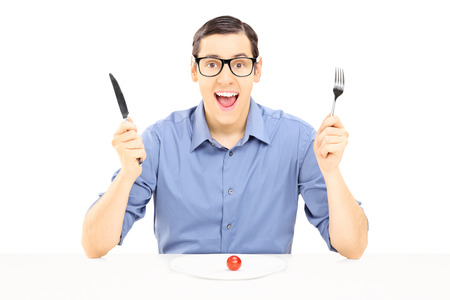 Young man holding a fork and spoon eating cherry tomato isolated on white  Stock Photo