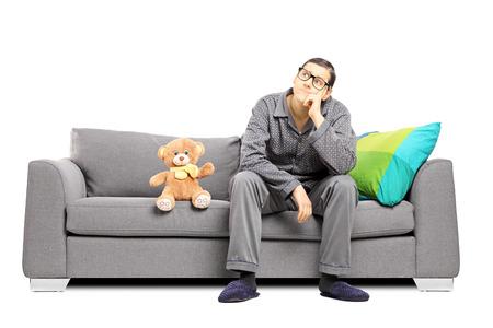 pijama: Joven en pijama profundas en el pensamiento sentado en un sofá con osito de peluche a su lado aislado en blanco