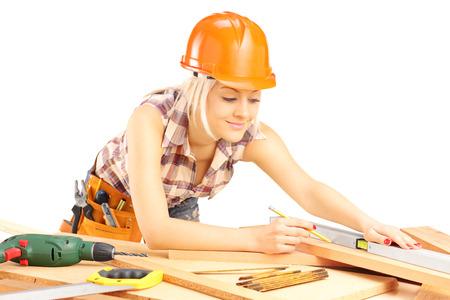 serrucho: Carpintero femenino rubio medir un listón aislado en fondo blanco Foto de archivo