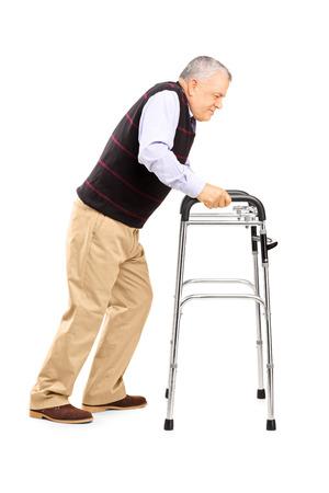 Volledige lengte portret van een oude man die worstelt om te bewegen met rollator op een witte achtergrond
