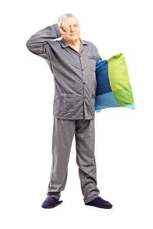 late 50s: Full length portrait of sleepy middle aged man in pajamas holding a pillow isolated on white background