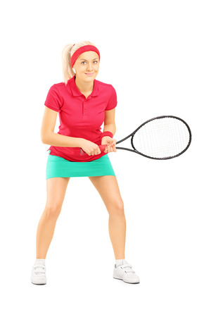 Full length portrait of young female tennis player holding a racket isolated on white background photo