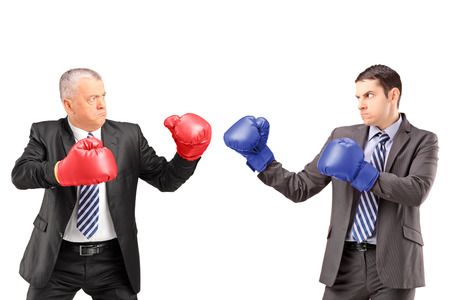 boxers: Mature businessman with red boxing gloves ready to fight his coworker isolated on white background