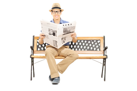 Young man seated on a wooden bench holding newspaper and looking at camera isolated on white background photo