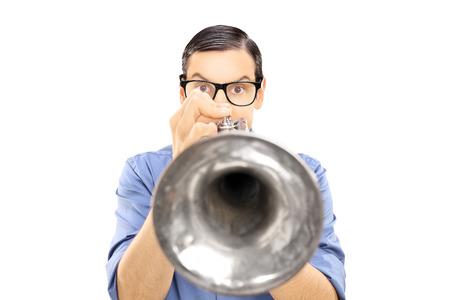 cuernos: Joven músico masculino que sopla en una trompeta aisladas sobre fondo blanco