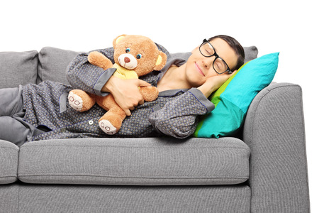 Young guy sleeping on sofa holding a teddy bear isolated on white background