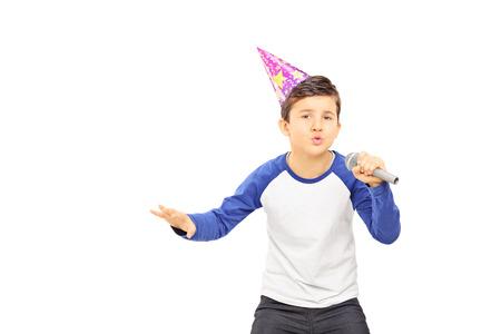 niño cantando: Chico joven con sombrero de fiesta de canto en el micrófono aislado en el fondo blanco