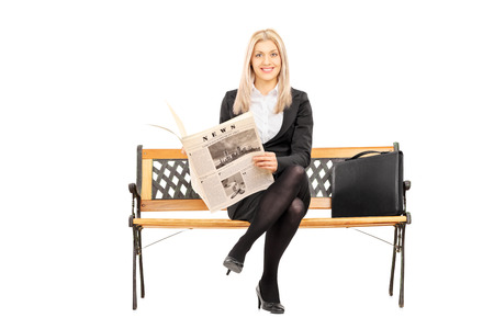 Young businesswoman seated on a bench holding newspaper isolated on white background photo