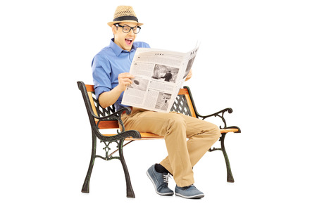 dazzled: Surprised young man reading the news seated on a bench isolated on white background