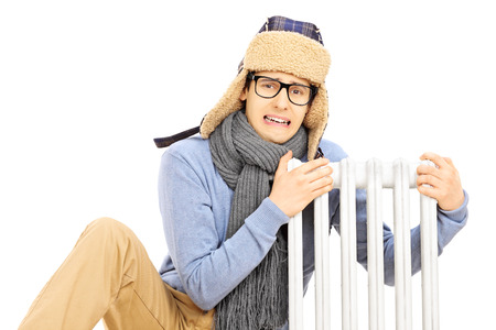 Chilled young man with winter hat sitting next to a radiator isolated on white  photo