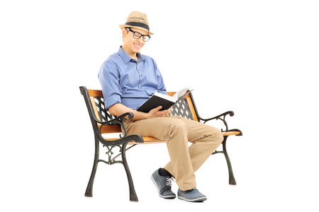 Young man with glasses reading a book on wooden bench isolated on white  photo