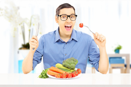 Young man eating a healthy meal, at home photo