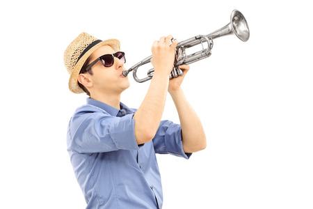 Jonge mannelijke muzikant speelt trompet geà ¯ soleerd op wit