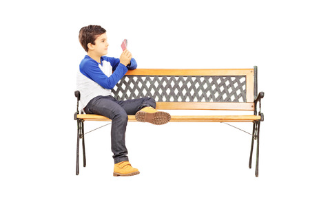 Young boy seated on wooden bench and playing cards with imaginary friend isolated on white
