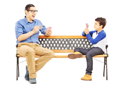 Young boy playing cards with his older cousin seated on bench isolated on white  Stock Photo - 25356371