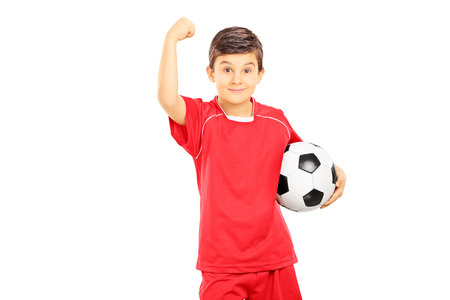 Young boy in sportswear holding soccer ball and gesturing with his hand, isolated on white