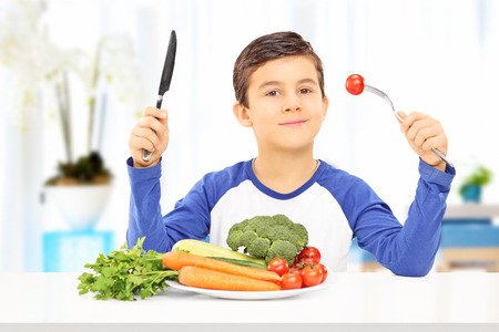 Young boy eating healthy meal seated at a table photo