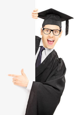 faculty: Male graduate student peeking from behind a blank panel and pointing with finger isolated on white background Stock Photo