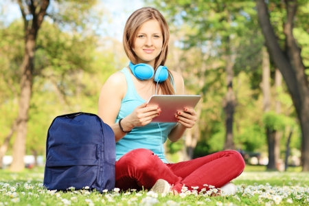 Young female student with headphones and tablet in a park photo