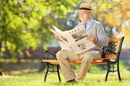 Senior gentleman with hat sitting on a wooden bench and reading a newspaper in a park photo