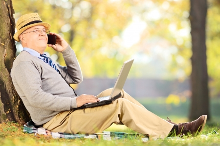 Senior man sitting in a park, talking on a mobile phone and working on a laptop photo